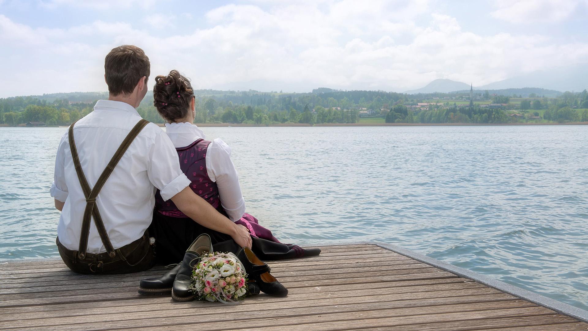Hochzeitsfotos vom Ehepaar auf einem Steg im Simssee und die Berge im Chiemgau im Hintergrund