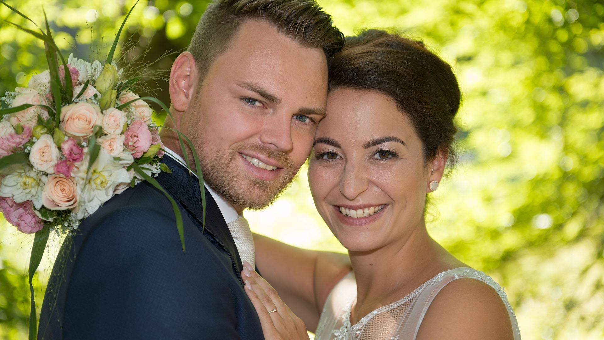 Hochzeitsfotos vom Ehepaar in der Sonne mit Brautstrauß