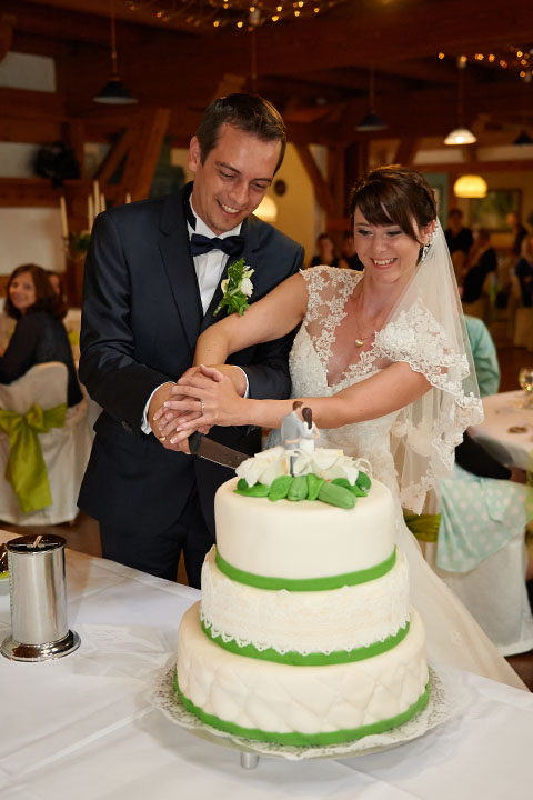 Reportage der Feier Ehepaar beim Kuchen und Hochzeitstorte anschneiden