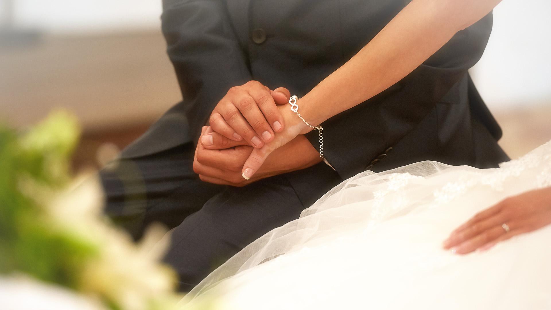 Reportage der Kirche Ehepaar Händchen halten bei der Trauung