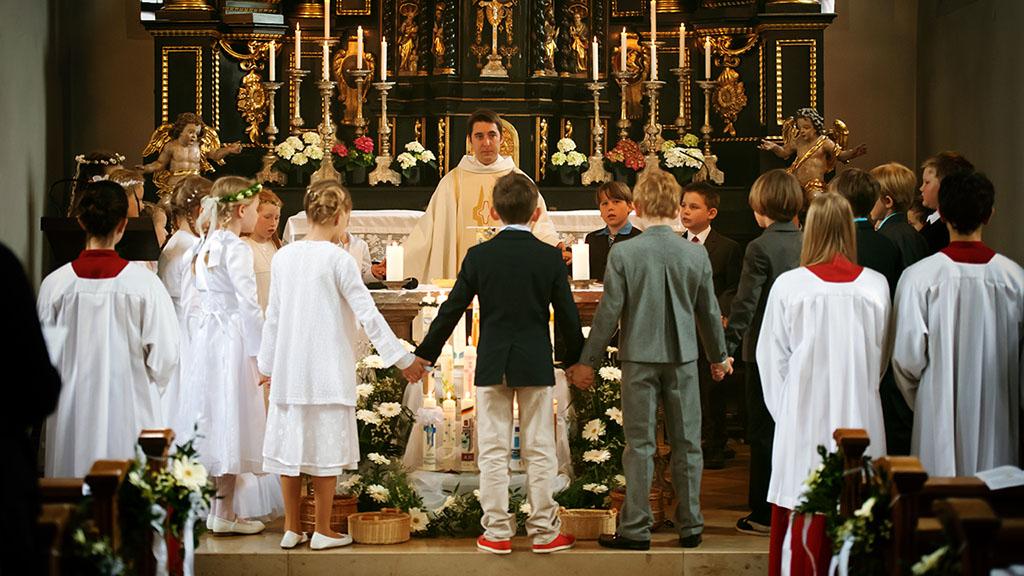 Reportage Kommunionskinder stehen im Gebet zusammen um den Altar