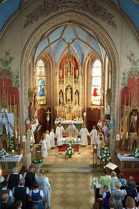 Reportage Kommunionkinder stehen im Gebet zusammen um den Altar