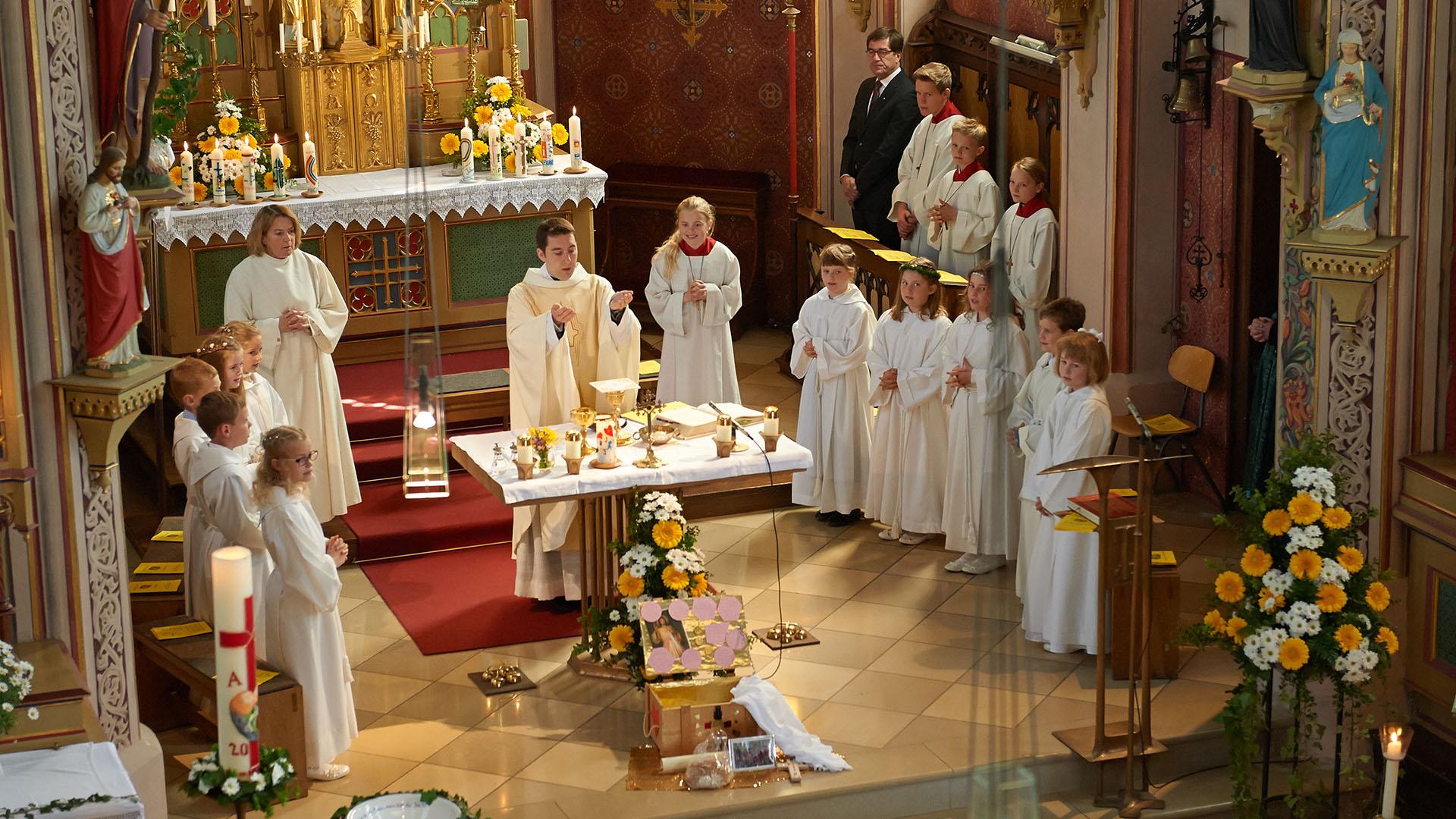Reportage Kommunionskinder stehen während der Wandlung um den Altar