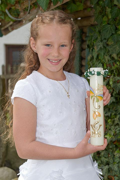 Portraits von Kommunionkind im Kleid mit Kerze